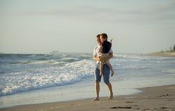 Young happy father holding in his arms little son walking on beach sand in front of sea waves Royalty Free Stock Photos