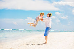 Young happy father holding little son in his arms. Putting him up standing barefoot at the beach with ocean and beautiful clouds on background. Having fun with royalty free stock photo