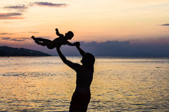Young happy father holding up in his arms little son putting him up at the beach in barefoot standing in front of sea waves wet sa stock image