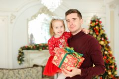 Young happy father keeping little daughter with present, Christmas tree in background. stock photo