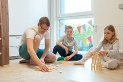 Young happy father playing with his two cute children with wooden blocks stock images
