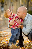Young happy father playing with little cute son with tree leaves. Young happy father playing with excited little cute son with tree leaves in the park smiling Stock Photos