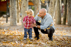 Young happy father playing with little cute son with tree leaves royalty free stock image