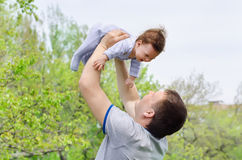 Young and happy father raising her baby. In the park Royalty Free Stock Images