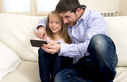 Young happy father showing sweet little girl using internet on mobile phone having fun together Royalty Free Stock Photography