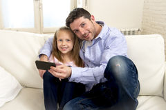 Young happy father showing sweet little girl using internet on mobile phone having fun together Stock Photo