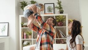 Young happy father throws up his baby daughter playing with her alongside her mother slow motion stock video footage