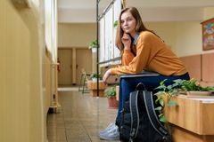 Young female college student sitting in the hallway at her school. Education concept. Young happy female college student sitting in the hallway at her school Stock Photo