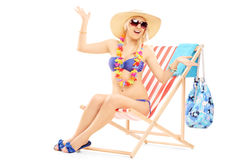 Young happy female with a hat posing on a beach chair stock images