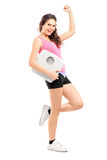 Young happy female holding a weight scale. Full length portrait of a young happy female holding a weight scale on white background stock images