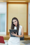 Young happy female makes some notes in notepad.  Royalty Free Stock Photography
