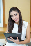 Young happy female makes some notes in notepad.  Royalty Free Stock Images