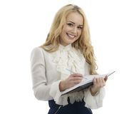 Young happy female makes some notes in notepad, isolated on whit. E Royalty Free Stock Photo