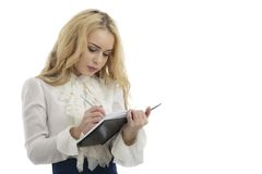 Young happy female makes some notes in notepad, isolated on whit Royalty Free Stock Photos