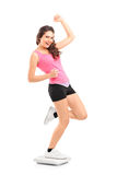 Young happy female standiong on a weight scale Royalty Free Stock Image