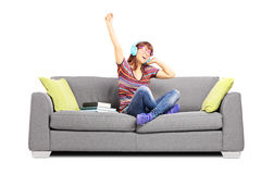 Young happy female student listening music seated on a sofa Stock Photos