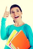 Young happy female student is pointing up Royalty Free Stock Image
