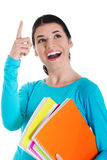 Young happy female student is pointing up and holding workbooks. Royalty Free Stock Image