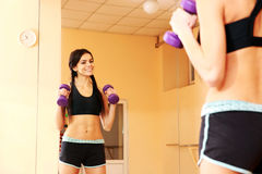 Young happy fit woman doing exercises with dumbells Stock Photo