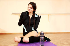 Young happy fit woman resting on yoga mat Stock Photography
