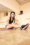 Young happy fit woman sitting on the floor Stock Image