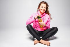 Young happy fit woman sitting with water bottle Royalty Free Stock Photography