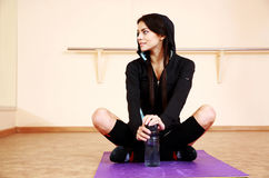 Young happy fit woman sitting on yoga mat Stock Images