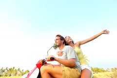 Young happy free couple in love on scooter. Multiracial young couple dating driving on scooter together during summer holidays vacation. Asian woman, Caucasian Royalty Free Stock Photography