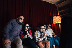 Young happy friends in 3d glasses watch tv at home. Company of five young happy friends in 3d glasses on couch watch movie on tv at home. Fun, entertainment Stock Image