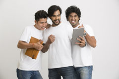 Young happy friends happily looking at pc tablet Royalty Free Stock Photo