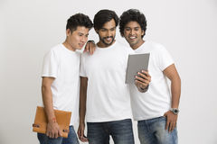 Young happy friends happily looking at pc tablet Royalty Free Stock Photography