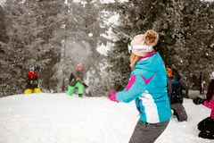 Happy friends having snow fighting and fun in snowy mountain Stock Image