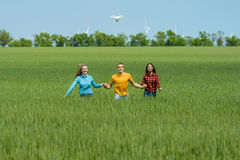Young happy Friends running on green wheat field Stock Photo