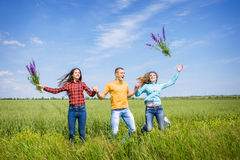 Young happy Friends running on green wheat field Royalty Free Stock Photography