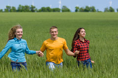 Young happy Friends running on green wheat field Royalty Free Stock Image