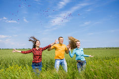 Young happy Friends running on green wheat field Stock Photography