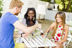 Young and happy friends sitting talking at a table Stock Photography