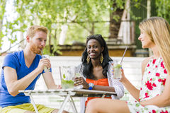 Young and happy friends sitting talking at a table Stock Photo