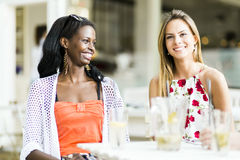 Young and happy friends sitting talking at a table Royalty Free Stock Photography
