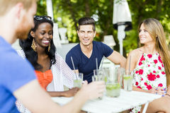 Young and happy friends sitting talking at a table Stock Images