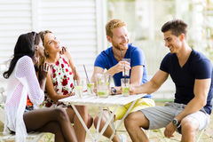 Young and happy friends sitting talking at a table Royalty Free Stock Photos