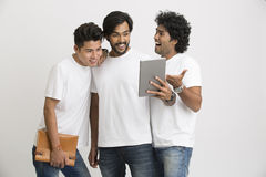 Young happy friends surprisingly looking at pc tablet Stock Photos