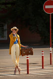 Young happy funny dressed woman. Young happy funny (vintage) dressed woman with retro suitcase stands on the street near red small columns Royalty Free Stock Photography