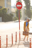 Young happy funny dressed woman. Young happy funny (vintage) dressed woman with retro suitcase stands on the street near red small columns and road sign Stock Image