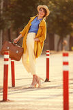 Young happy funny dressed woman. Young happy funny (vintage) dressed woman with retro suitcase stands on the street near red small columns Royalty Free Stock Photos