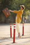 Young happy funny dressed woman. Young happy funny (vintage) dressed woman throws retro suitcase on the street near red small columns Stock Image