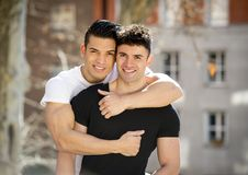 Young happy gay men couple cuddling on street free homosexual love concept Stock Images