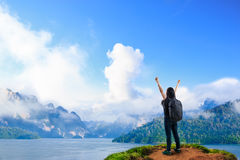 Young happy girl with backpack standing near big river with rais Royalty Free Stock Image