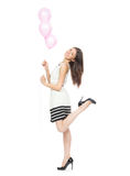 Young happy girl with balloons as a present for birthday. Party smiling and looking at the corner on a white background Stock Photos