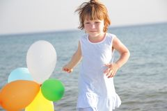 Young happy girl with balloons on sea background Royalty Free Stock Photo